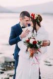 Couples nuptiales de nouveaux mariés heureux se tenant sur la rive de caillou avec Forest Hills comme fond Image stock