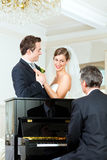 Couples nuptiales devant un piano Images libres de droits