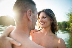 Couples nus affectueux étreignant dans le lac d'été Images libres de droits
