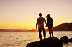 Couples observant le soleil par la mer image stock