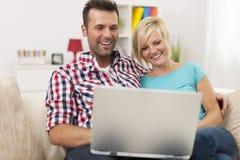 Couples observant quelque chose sur l'ordinateur portable Image stock