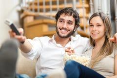 Couples observant un film sur le divan Image libre de droits