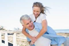 Couples occasionnels ayant l'amusement par la mer Image libre de droits