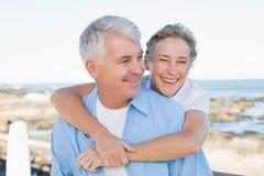 Couples occasionnels ayant l'amusement par la mer Photographie stock libre de droits