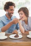 Couples occasionnels ayant le café et le gâteau ensemble Photographie stock