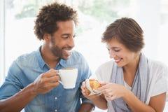 Couples occasionnels ayant le café et le gâteau ensemble Images stock