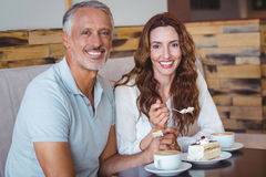 Couples occasionnels ayant le café et le gâteau ensemble Photographie stock libre de droits