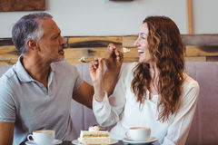 Couples occasionnels ayant le café et le gâteau ensemble Photo stock