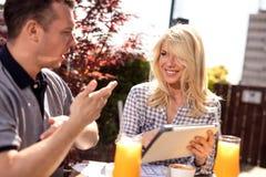 Couples occasionnels d'affaires en café travaillant au comprimé numérique image libre de droits
