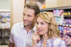 Couples occasionnels de sourire regardant l'étagère images libres de droits