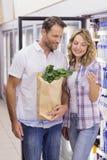 Couples occasionnels de sourire regardant la bouteille d'eau Photo stock