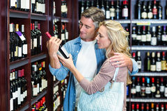 Couples occasionnels de sourire regardant la bouteille de vin Photo stock