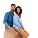 Couples occasionnels de sourire se reposant ensemble sur la boîte en bois Photo stock