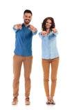 Couples occasionnels heureux dirigeant leurs doigts Images stock