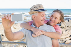 Couples occasionnels heureux prenant un selfie par la côte Images libres de droits