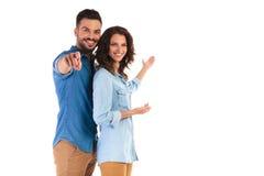 Couples occasionnels heureux vous invitant à quelque chose Image stock