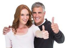 Couples occasionnels montrant des pouces  images stock