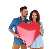 Couples occasionnels montrant un grand coeur rouge Photographie stock