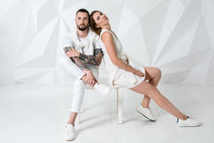 Couples occasionnels près d'un mur, d'un homme et d'une femme blancs dans l'habillement blanc Photo stock