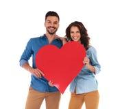 Couples occasionnels riants tenant un grand coeur rouge Photographie stock libre de droits