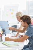 Couples occasionnels utilisant l'ordinateur dans le bureau Images libres de droits