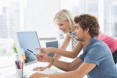 Couples occasionnels utilisant l'ordinateur dans le bureau Photos stock