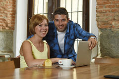 Couples ou amis au café fonctionnant avec l'ordinateur portable le matin heureux Photographie stock