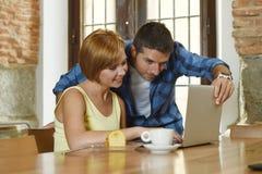 Couples ou amis au café fonctionnant avec l'ordinateur portable le matin heureux Photo stock