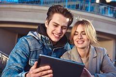 Couples ou amis heureux étreignant et partageant un comprimé dans la rue Photo stock