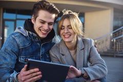 Couples ou amis heureux étreignant et partageant un comprimé dans la rue Images libres de droits