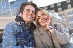 Couples ou amis heureux étreignant et partageant un comprimé dans la rue Photographie stock libre de droits