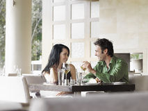 Couples parlant au-dessus du vin au restaurant Photo stock