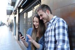 Couples parlant du contenu en ligne de t?l?phone intelligent dans la rue photo stock