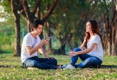 Couples parlant et à l'aide du téléphone portable en parc Images stock