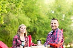 Couples parlant et riant sur des vacances en camping Photographie stock libre de droits
