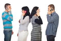 Couples parlant par des mobiles de téléphone Photographie stock libre de droits