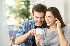 Couples partageant la musique du téléphone intelligent Images libres de droits