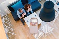 Couples partageant la pizza et la consommation Photographie stock