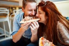 Couples partageant la pizza et la consommation Images stock