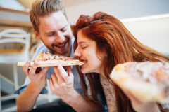 Couples partageant la pizza et la consommation Photographie stock libre de droits