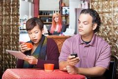 Couples partant furtivement avec des dispositifs de Digital Photographie stock libre de droits