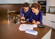 Couples passant en revue leurs comptes avec un numérique Images stock