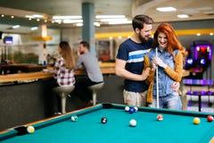 Couples passant le temps ensemble en jouant la piscine photographie stock libre de droits