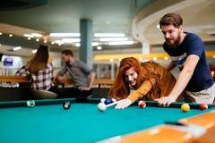 Couples passant le temps ensemble en jouant la piscine photos stock
