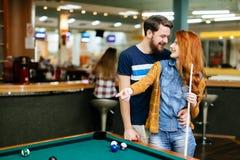 Couples passant le temps ensemble en jouant la piscine images stock