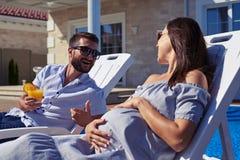 Couples passant le temps sur des chaises longues devant la maison photographie stock libre de droits