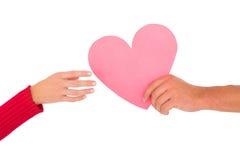 Couples passant un coeur de papier Photos stock