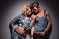 Couples passionnés se tenant contre le mur gris de studio Image stock