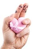 Couples peints sur les doigts et le boîte-cadeau de l'homme Images stock