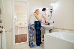 Couples pendant le matin dans la salle de bains faisant l'hygiène personnelle Image stock